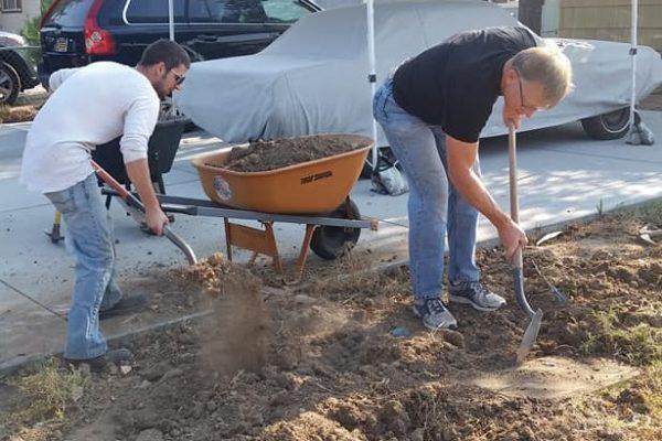 2 men filling a wheelbarrow